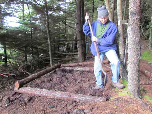 Michelle digs the ground level for the first tier of logs (Photo: Mark A. Zeiger).