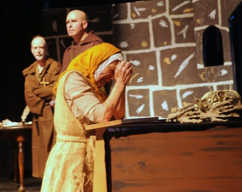 As Brother Martin (John Hunt) and Father Charles (Mark Zeiger) contemplate the danger, a peasant woman (Judith McDermott) prays for their safety (Photo: KHNS News Staff).