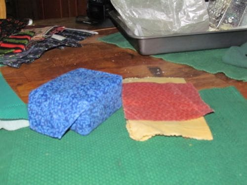 Beeswax wraps on a block of cheese (l) and smaller jobs. The one on top fits under a ring to seal a jar (Photo: Mark A. Zeiger).