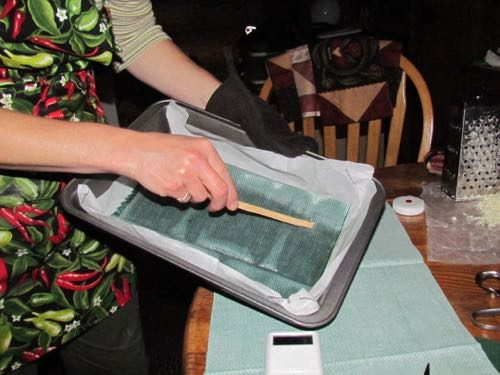 Michelle spreads melted wax around cloth with a stick (Photo: Mark A. Zeiger).